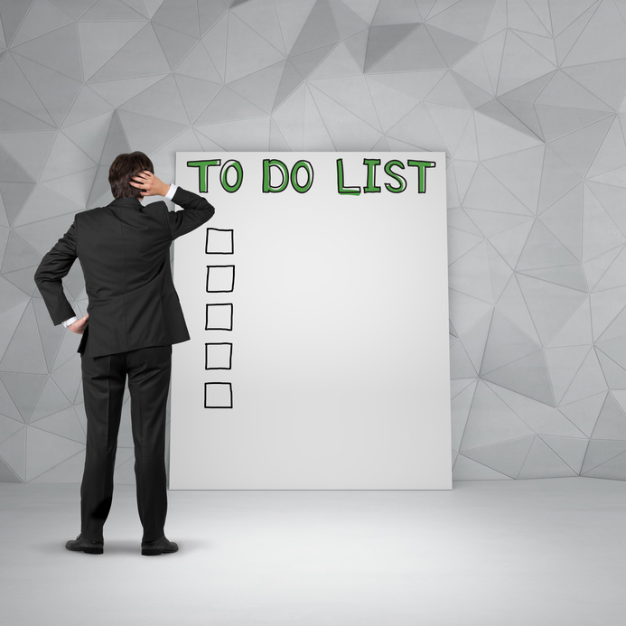 Thinking businessman standing in front of to do list